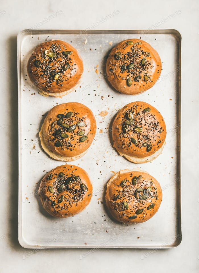 Freshly baked buns with seeds for cooking burgers, top view