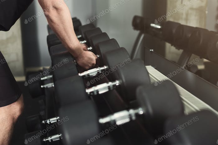 Unrecognizable man taking dumbbells at gym