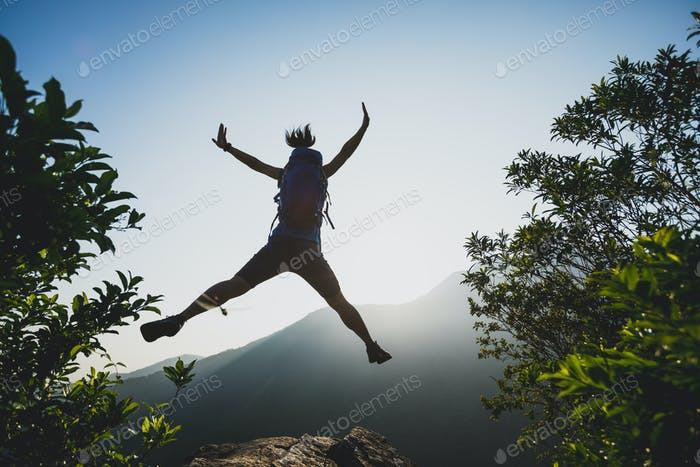 Hiker jumping on sunrise mountain top cliff edge