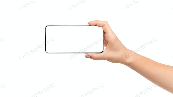 Woman's hand holding modern smartphone with blank screen for mockup