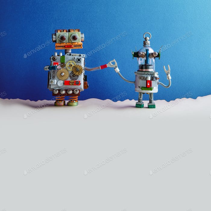 Two funny toy robots holding hands. Fantastic blue beige landscape. The big robot holds the hand of