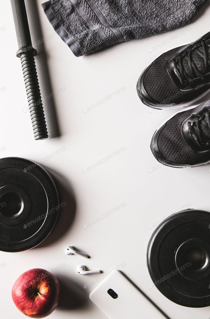 Towel, sneakers, and smartphone with headphones on a white background