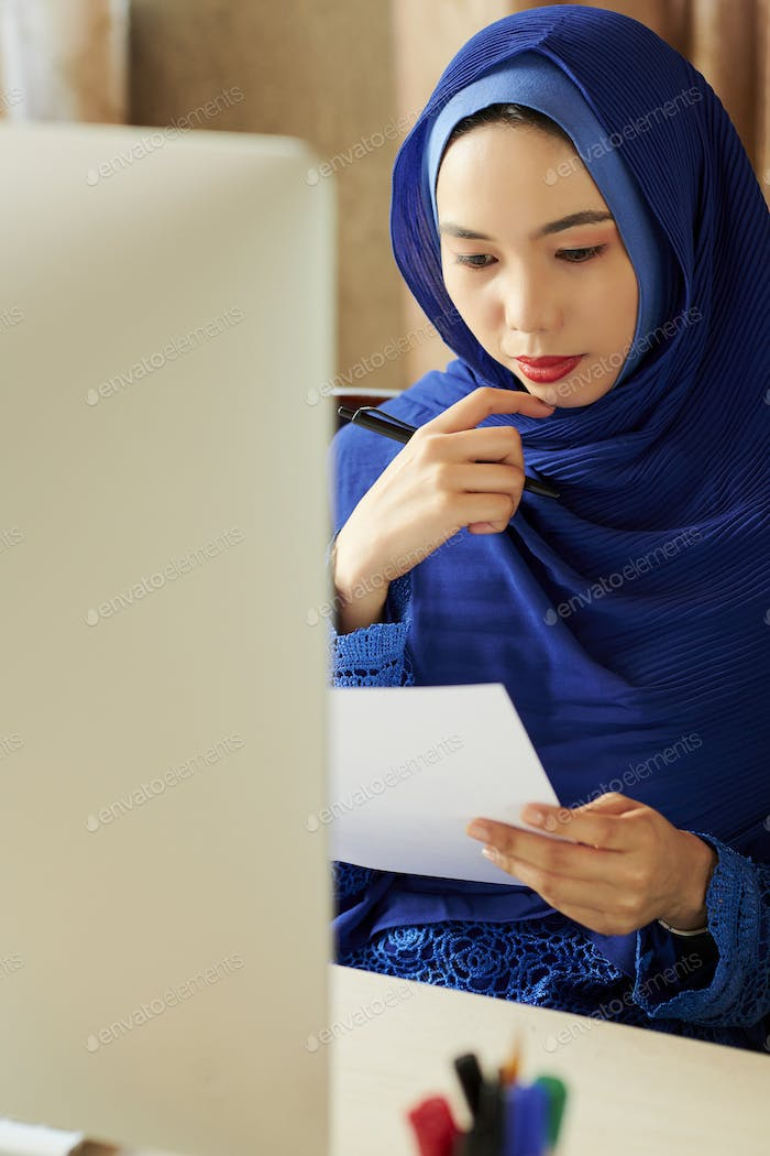 Muslim businesswoman reading letter