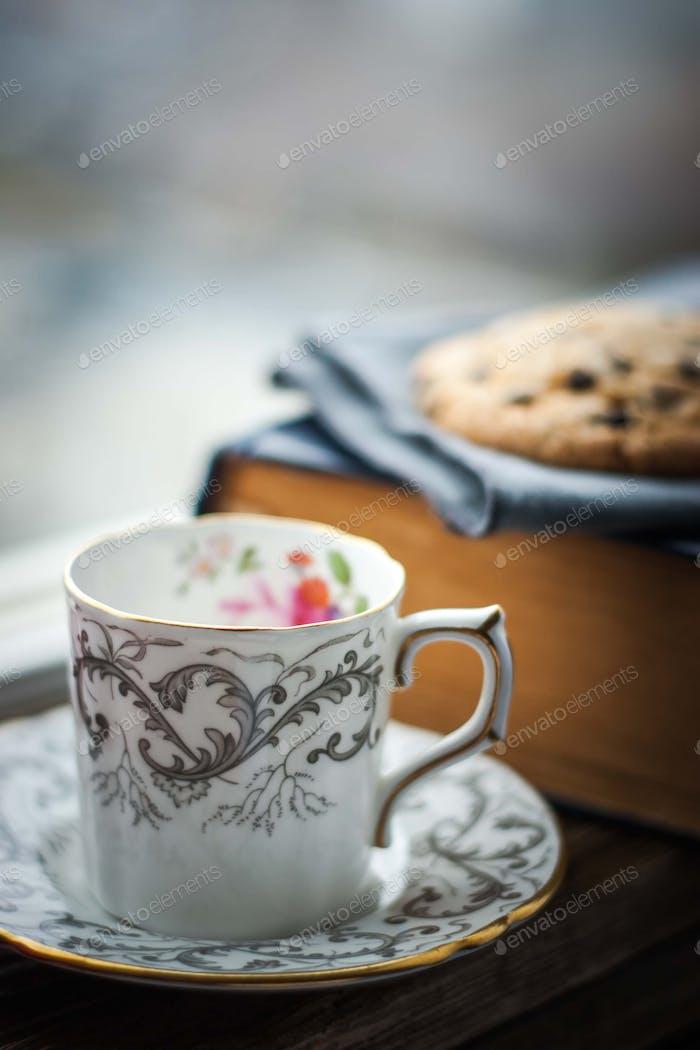 Kaffeetasse mit verschwommenen Plätzchen und altem Buch