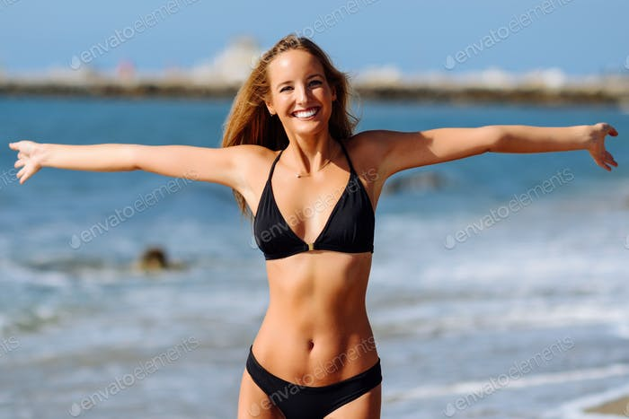 Young blonde woman with beautiful body in swimwear on a tropical