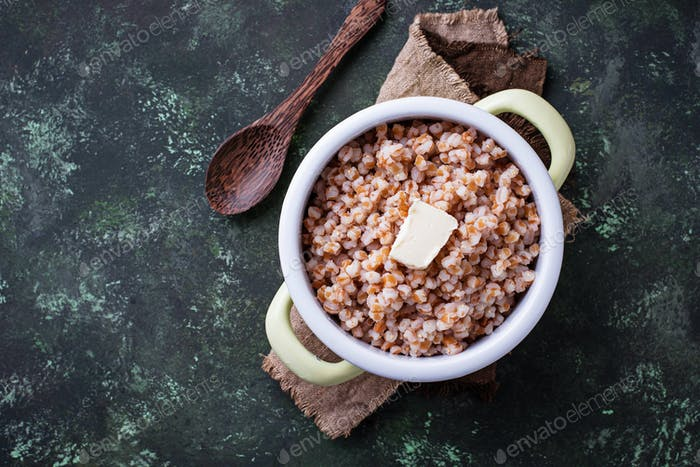 Barley porridge with butter in green pot