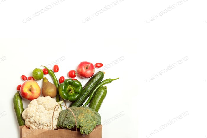 Paper bag of different healthy farm vegetables and fruits isolated on a white background.