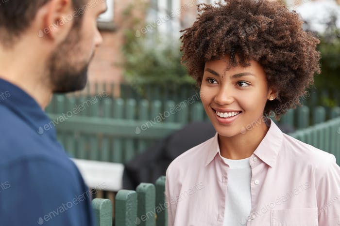 Happy dark skinned girl meets her groupmate, have lively talk outdoor, look joyfully at each other,