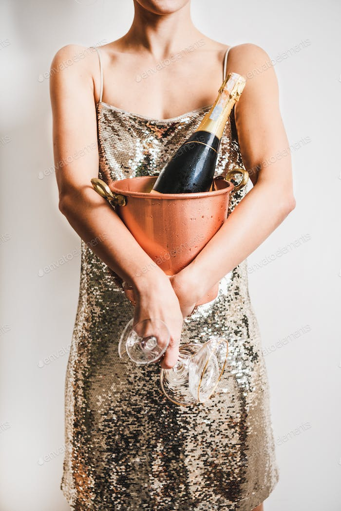Woman in golden dress holding bucket with ice for champagne