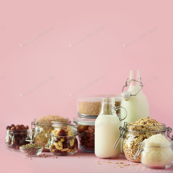 Vegan substitute dairy milk. Glass bottles with non-dairy milk and ingredients over pink background