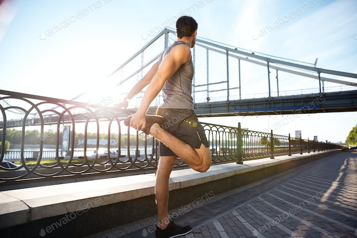 Side view of a sports man stretching with bridge railing