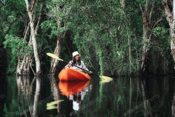 Asian traveler woman kayaking in Mangrove forest of Botanical Garden, Thailand.