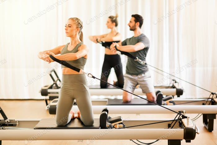 Group of people doing pilates torsion rotation exercises