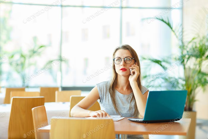 Woman working with a laptop and talking on the cell phone