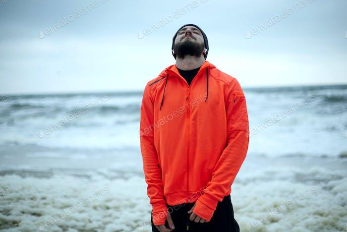 Mann im warmen orangefarbenen Mantel genießt einen morgendlichen Spaziergang über das