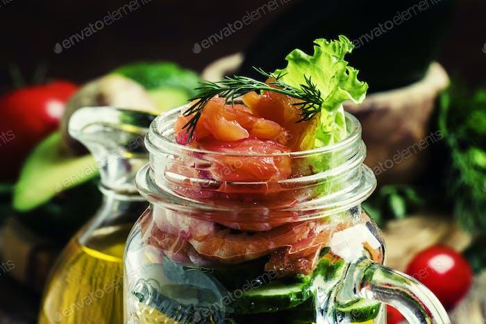 Salat mit Gemüse und Fisch, serviert in einem Glas, selektiver Fokus