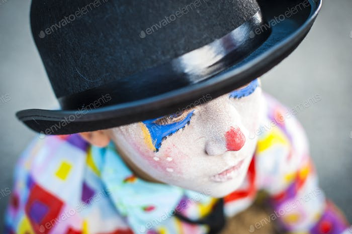 alone boy 8/6 years old with clown makeup - sad wearing hat