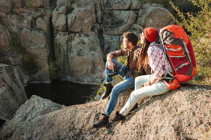 Adventure couple sitting on a rock