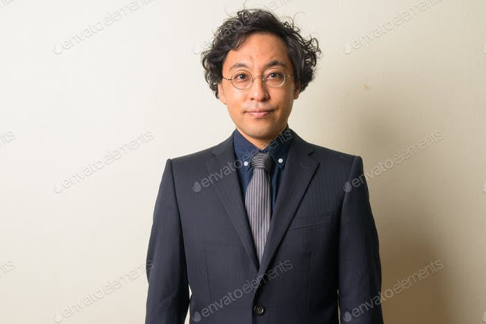 Face of Japanese businessman in suit with curly hair