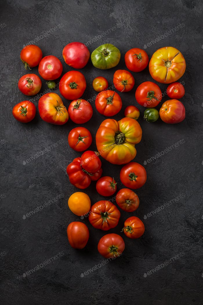 Letter T made with ripe tomatoes on a black background, creative flat lay healthy food concept
