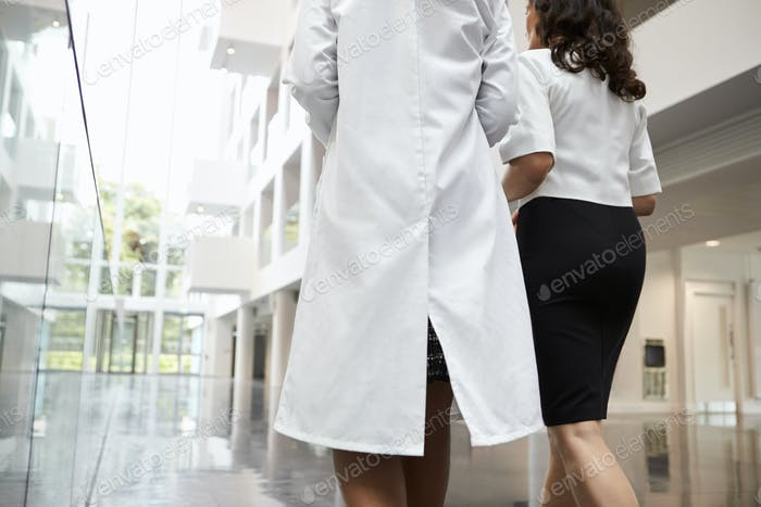 Rear View Of Doctors Talking As They Walk Through Hospital