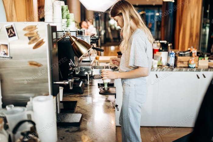 A young beautiful thin blonde,dressed in casual outfit,is cooking coffee in a popular coffee shop