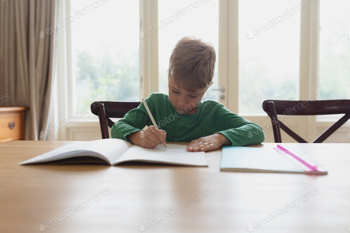 Front view of cute Caucasian boy doing homework at dining table in a comfortable home
