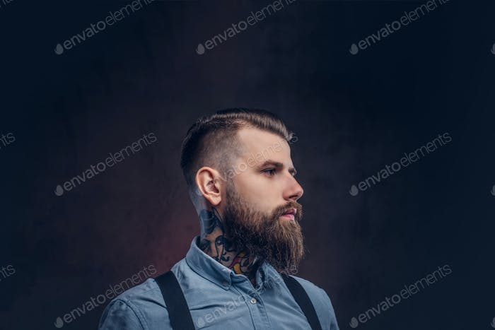 Портрет красивого старомодного хипстера в синей рубашке и подтяжках, позирует в студии.