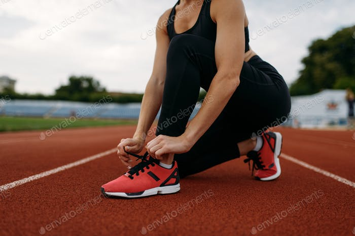 Female runner tying her shoelaces on stadium
