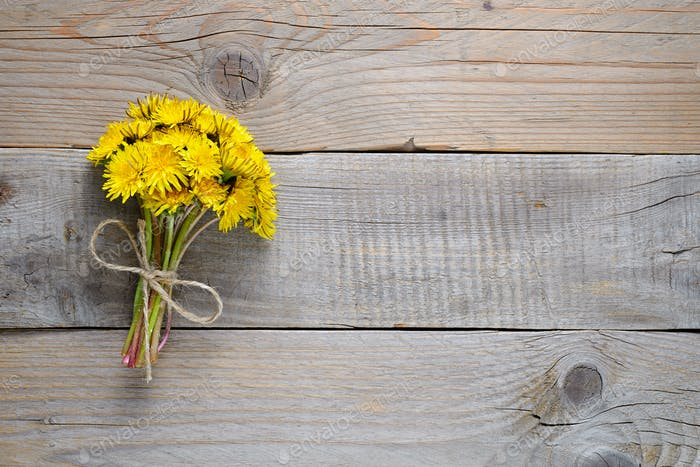 Bouquet of dandelion flowers on wooden background