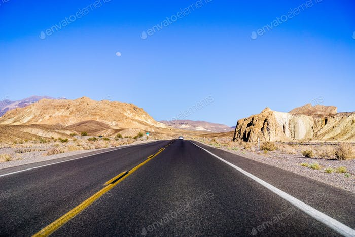 Travelling through Death Valley National Park, moon rising up in the sky; California