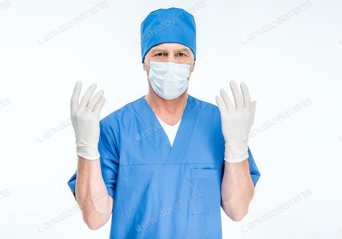 Reife männliche Chirurg in Maske und chirurgischen Handschuhen Blick auf Kamera isoliert auf weiß