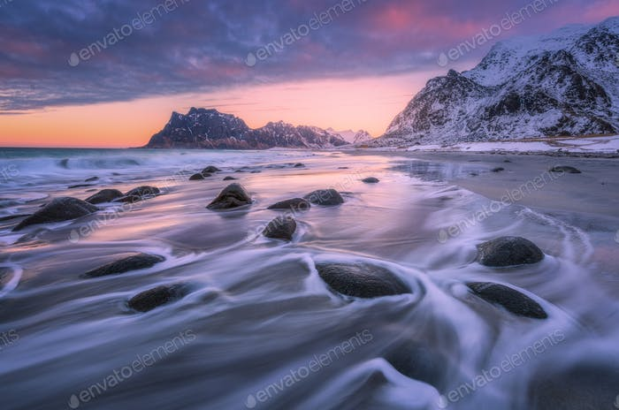 Beautiful sandy beach with stones in blurred water at sunset