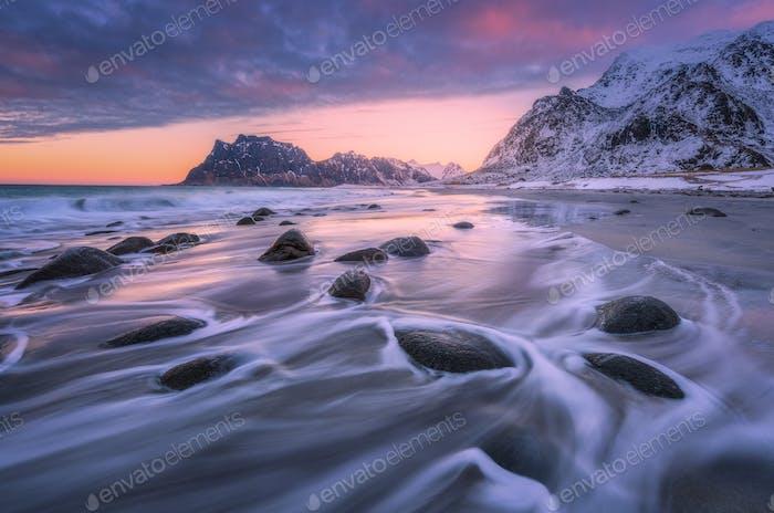 Schöner Sandstrand mit Steinen in verschwommenem Wasser bei Sonnenuntergang