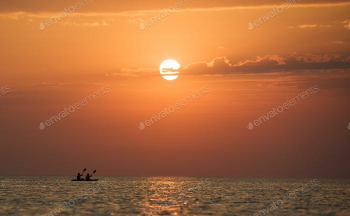 Meerlandschaft von stiller Meeresoberfläche, Männer auf Boot und goldener Sonnenuntergang im Himmel