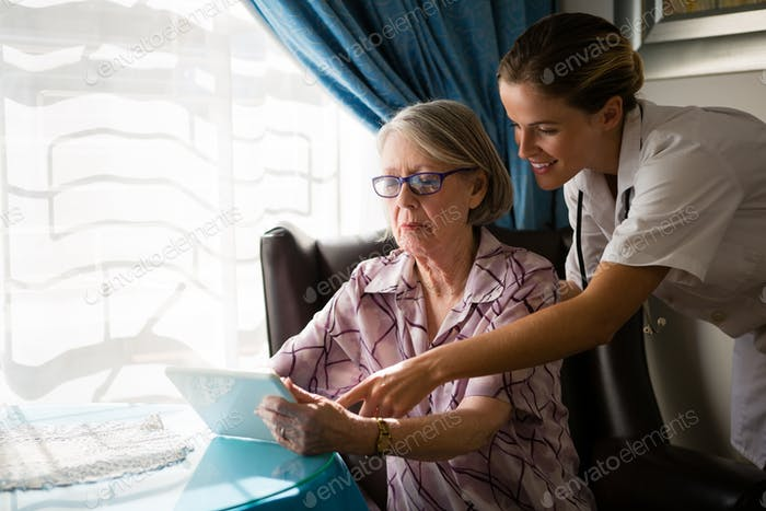 Female doctor assisting woman in using digital tablet