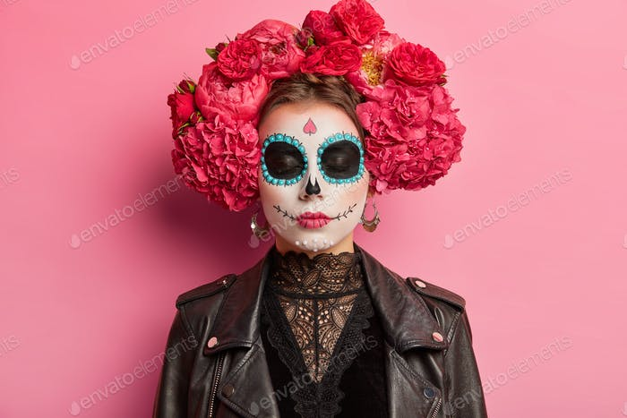 Indoor shot of calm woman with closed eyes bright makeup prepares for Mexican holiday has sugar skul