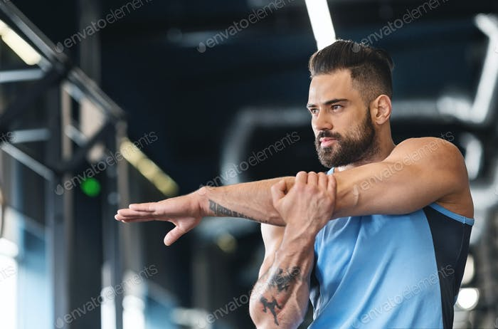 Sportsman stretching his hands before workout training at gym