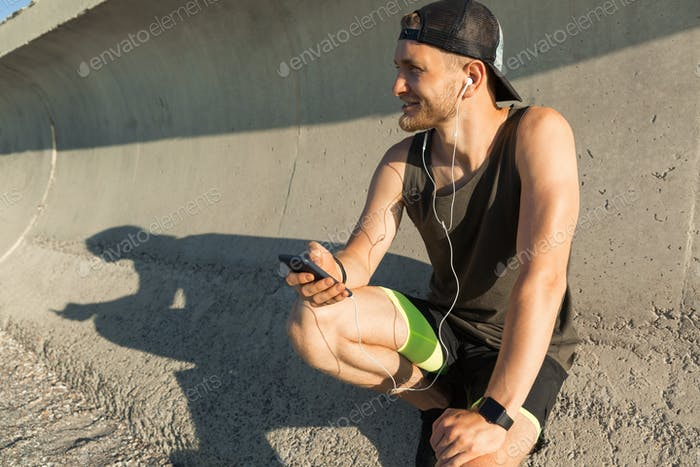 Athletic young sportsman listening to music with earphones