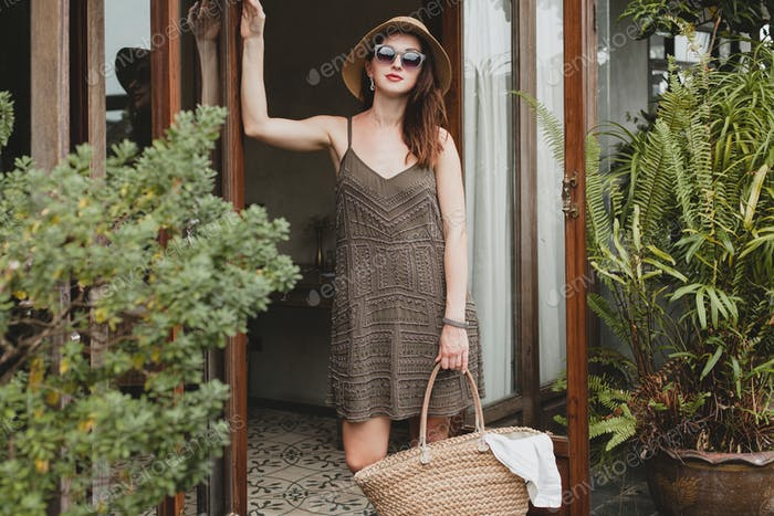 young beautiful stylish woman in resort hotel, wearing trendy dress