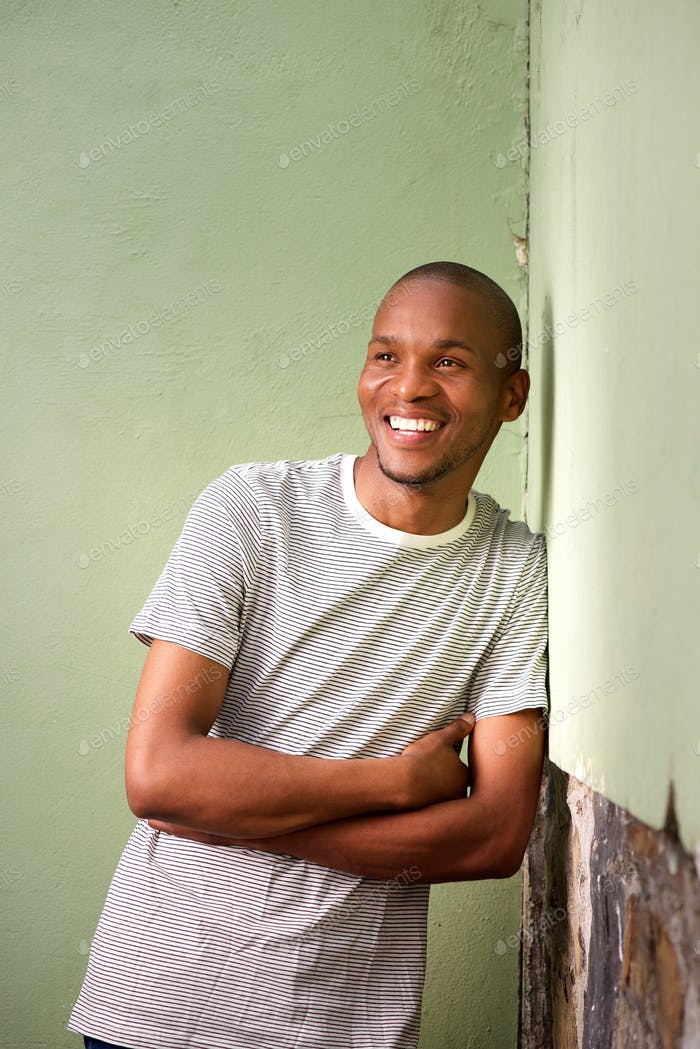 young afro american man leaning to wall and smiling