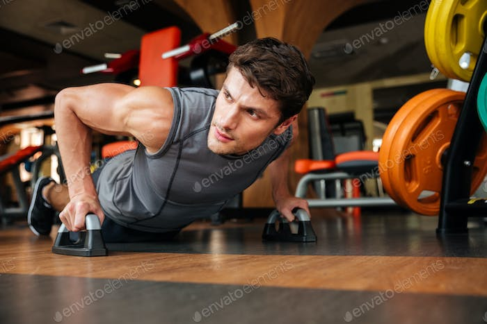 Sportsman doing push-up exercises in gym