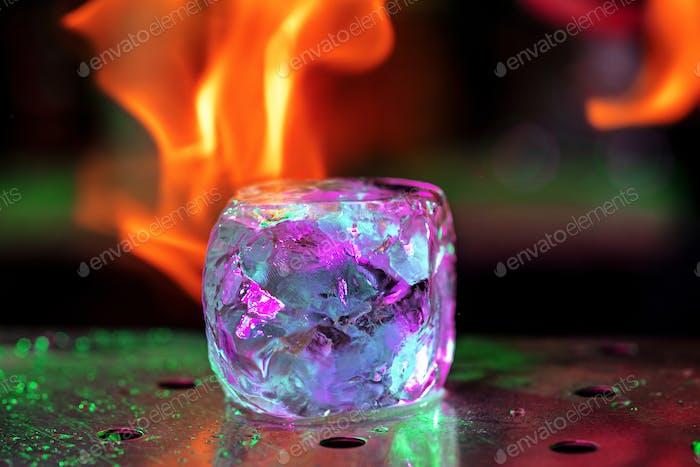 Nahaufnahme großes schmelzendes Stück Eis auf der Bar Theke in Feuerflammen darauf, Vorbereitung auf einen Cocktail