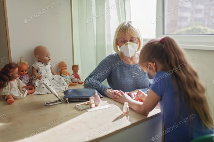 Multigenerational relations, girl and granny wearing respirators doing makeup together, new normal