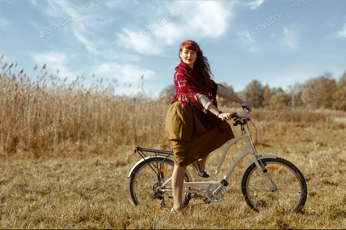 Pretty girl riding bicycle in field