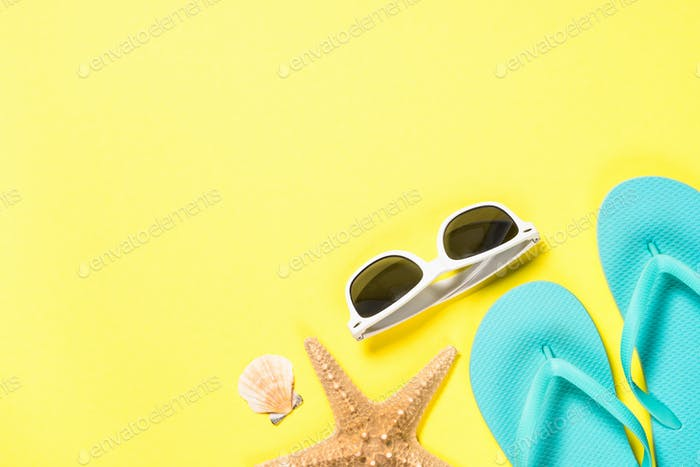Blue flip flops, sunglasses and starfish on yellow background