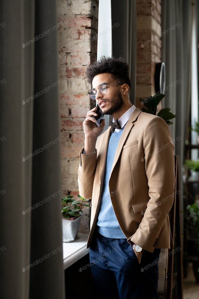 Confident mixed race businessman talking by phone
