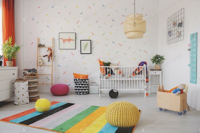 Poufs on colorful rug in scandi baby's room interior with cradle