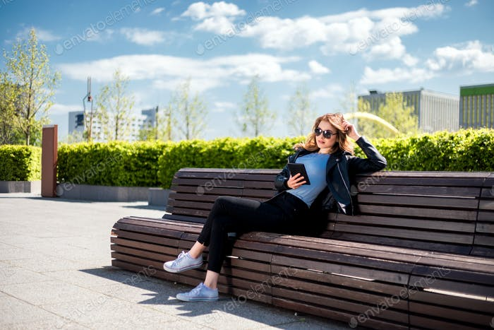 Woman sitting on bench among urban space and using tablet in the city