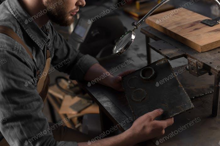 Cropped Shot of Workman Blick mit Lupe Blick auf Metall Teil